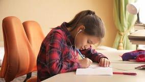 Тонизированное фото девочка-подростка слушая к музыке и поя пока делающ домашнюю работу Стоковая Фотография