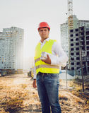 Тонизированное фото инженера представляя против строительной площадки на заходе солнца Стоковое Изображение RF