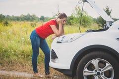 Тонизированное фото молодой женщины стоя на сломленном автомобиле на дороге сельской местности и смотря перегретый двигатель Стоковая Фотография RF
