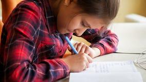 Тонизированное фото сочинительства девушки в тетради с прописями с ручкой чернил Стоковые Изображения RF