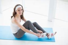 Тонизированные ботинки женщины нося на циновке тренировки на студии фитнеса стоковая фотография rf