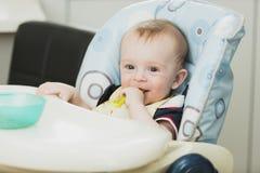 Тонизированный портрет усмехаясь младенца сидя в высоком стульчике и есть g Стоковые Фото