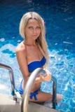 Тонкая белокурая женщина получает suntan около бассейна стоковые изображения