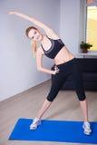 Тонкая гибкая женщина делая протягивающ тренировку дома Стоковое Изображение