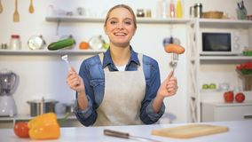 Тонкая девушка выбирая между овощем и сосиской, натуральными продуктами против продуктов gmo акции видеоматериалы