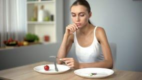 Тонкая девушка смотря таблетки анти--тучности, одержимость с потерей веса, наркоманией стоковые изображения