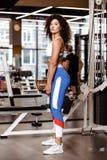 Тонкая девушка с темным вьющиеся волосы одетым в sportswear стоит с тяжелой гантелью в ее руках в современном стоковое изображение