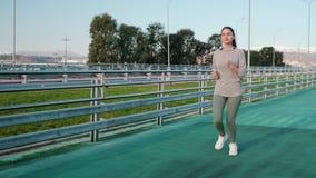 Тонкая девушка jogging на следе стадиона в солнечном дне, сток-видео
