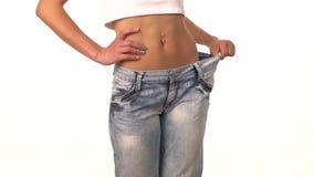 Тонкая девушка в больших джинсах, показывая ее теряет вес сток-видео