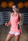 Тонкая девушка в пинке резвится форма с скача веревочкой на предпосылке спортзала Мышцы здания и концепция тренировки стоковое фото rf