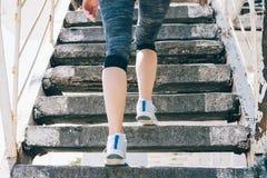 Тонкая девушка в тапках и лестницах sportswear взбираясь, конце-вверх стоковое фото