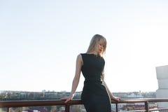 Тонкая девушка в черном платье на мосте Стоковая Фотография RF