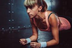 Тонкая девушка спортсмена молодой женщины фитнеса делая планку Стоковое Изображение RF