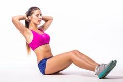 Тонкая девушка спортсмена молодой женщины фитнеса делая тренировку планки с ногами Стоковая Фотография RF