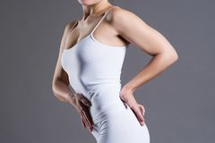Тонкая женщина в белом нижнем белье на серой предпосылке студии, совершенное женское тело стоковое изображение