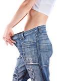 Тонкая женщина в слишком большой парах голубых джинсов Стоковые Фото