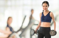 Тонкая женщина держа гантель на спортзале конспекта нерезкости стоковая фотография