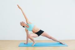 Тонкая женщина делая бортовое представление йоги планки Стоковое фото RF
