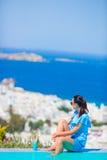 Тонкая женщина прикладывая солнцезащитный крем на ее ногах, сидя на краю городка Mykonos предпосылки бассейна старого в Европе Стоковая Фотография RF