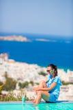 Тонкая женщина прикладывая солнцезащитный крем на ее ногах, сидя на краю городка Mykonos предпосылки бассейна старого в Европе Стоковые Фото