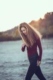 тонкая женщина при грязные длинные волосы нося черные джинсы и красную рубашку идя на ветреный день осени внешний на пляж Стоковая Фотография