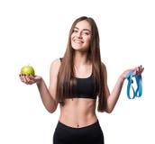 Тонкая и здоровая молодая женщина держа ленту измерения и яблоко изолированное на белой предпосылке Потеря веса и концепция диеты стоковое изображение