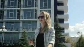 Тонкая и красивая маленькая девочка в костюме джинсовой ткани и высоких пятках идя в парк в замедленном движении акции видеоматериалы