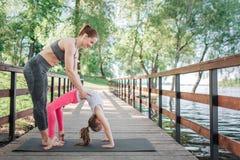Тонкая и крепкая женщина помогает ее студенту сделать представление моста Младенец делает то действительно хорошее Они работают Стоковое Изображение