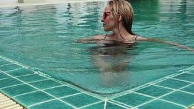 Тонкая красивая женщина приходит в бассейн гостиниц и caming вне Принципиальная схема каникулы лета видеоматериал