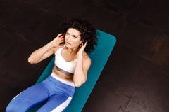 Тонкая курчавая темн-с волосами девушка одетая в одеждах спорт делая тренировки для прессы на циновке для фитнеса в спортзале стоковые фотографии rf