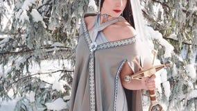 Тонкая модель с длинными черными волосами и мягкий макияж представляя для камеры, взгляды принцессы эльфа на ее отражении в лезви видеоматериал