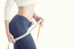 Тонкая молодая женщина измеряя ее тонкую талию с рулеткой стоковая фотография rf