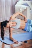 Тонкая молодая женщина фитнеса делая бортовую тренировку планки дома с smartphone Стоковое Фото