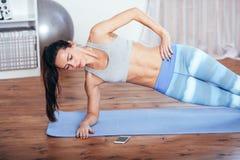 Тонкая молодая женщина фитнеса делая бортовую тренировку планки дома с smartphone Стоковые Фотографии RF