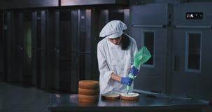 Тонкая очаровательная молодая женщина с черными длинными волосами украшает грациозно внутреннюю середину торта с приходить заморо акции видеоматериалы