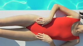Тонкая привлекательная дама в красном купальнике лежа около бассейна и загорая, солнцезащитный крем сток-видео