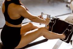 Тонкая темн-с волосами девушка одетая в черных спорт верхних и шортах разрабатывает на машине тренировки в спортзале стоковое фото