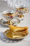 Тонкие блинчики на плите и чашке чаю Стоковая Фотография RF