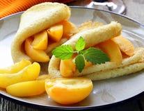 Тонкие блинчики (crepes) с персиками Стоковое Изображение