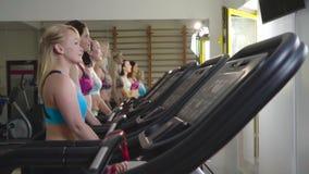 Тонкие женщины в одеждах спорт идут на третбан и смотрят вперед, замедленное движение сток-видео