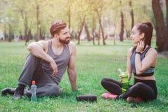 Тонкие и шикарные люди сидят совместно на траве объявление имея некоторую девушку остатков держит бутылку с водой alric стоковое фото