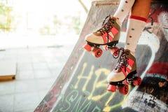 Тонкие ноги девушки носят длинные носки и розовые ролики Девушка сидящ и держащ колени ног совместно Стоковые Изображения RF