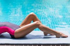 Тонкие ноги женщины загорают около бассейна Стоковое Изображение