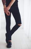 Тонкие ноги молодого человека нося сорванные джинсы и кожаные ботинки стоковое изображение rf
