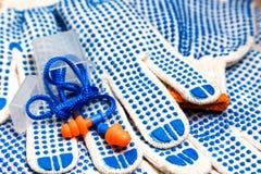 Тонкие перчатки работы с голубыми цыпками и берушями закрывают вверх Стоковые Изображения
