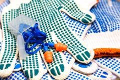 Тонкие перчатки работы с зелеными цыпками и берушями закрывают вверх Стоковая Фотография