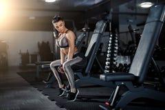 Тонкий, девушка культуриста, поднимает тяжелую гантель стоя перед зеркалом пока тренирующ в спортзале Спорт концепция, сало стоковое фото rf