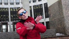 Тонкий парень в красной sportive куртке, солнечных очках поя рядом со столбцами гранита сток-видео