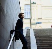Тонкий, привлекательный человек полагается на перилах, на лестницах красивейший смотреть outdoors вверх по детенышам женщины подз стоковое изображение