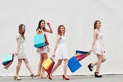 4 тонких друз женщин с хозяйственными сумками Стоковые Фотографии RF